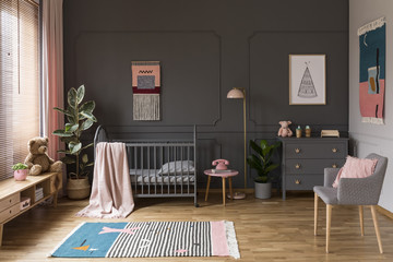 Real photo of a grey crib standing next to a pink stool, a lamp and cupboard in grey baby room interior also with armchair, rug and posters © Photographee.eu