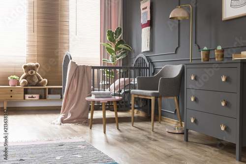 Leinwandbild Motiv Real photo of a cot standing next to an armchair, lamp and cupboard in dark and classic baby room interior