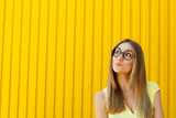 Portrait of a thoughtful girl wearing toy funny glasses looking up over yellow background at daylight - 213643541