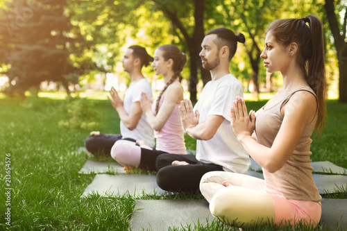 Leinwanddruck Bild Group of people meditating in park