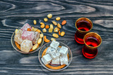 Traditional oriental sweets and traditional Turkish tea on a dark wooden background. Turkish desert-Rahat locum. - 213655355