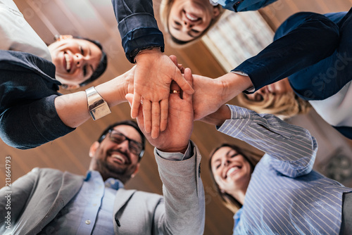 Team building, partnership, business success concept. Bottom view of business people putting hands together. © bnenin