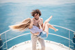 Hot young lovers starting foreplay on the bow of the luxury boat in open sea in summer. Young brunette man holding on hands sensual blonde woman. Outdoor portrait of sea travel recreation lifestyle.