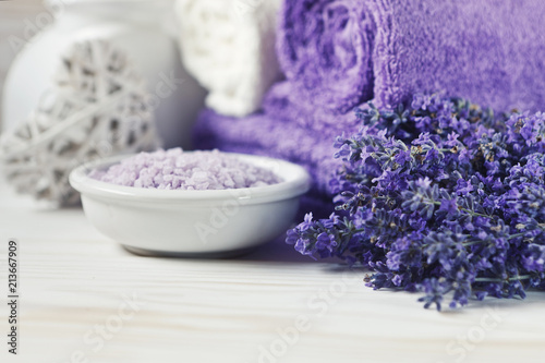 Fotobehang Spa Lavender flowers, aromatic sea salt and towels. Concept for spa, beauty and health salon, cosmetics store. Close up photo on white wooden background.