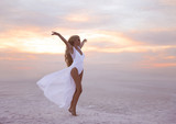 Wellness. Beautiful free confidence woman in white swimsuit enjoy summer vacation at sunset on the beach. Carefree blonde girl standing with arms outstretched in a gesture of freedom and excitement.