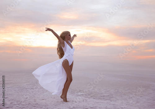 Leinwandbild Motiv Wellness. Beautiful free confidence woman in white swimsuit enjoy summer vacation at sunset on the beach. Carefree blonde girl standing with arms outstretched in a gesture of freedom and excitement.
