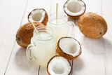 Refreshing coconut water in jars and coconuts on a wooden white background.