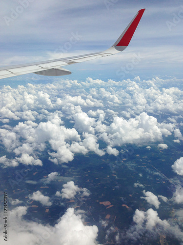 Views from the window of an airplane. Red and white wing of the plane, clouds, sky and land from high above. Business trip, holidays travel, vacation concepts - 213671197
