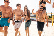 Friends walking across sandy court to the ocean after playing beach volleyball, to cool heated bodies after game, sharing positive emotions and happy moments of the game.
