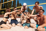 Give high five. Group of fit excited caucasian people talking in a circle, sitting on sand after volleyball game won. discussing goal, achieving team results. Teamwork, vacation, active life benefits - 213671936
