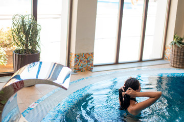 Calmness and harmony in air. Attractive young caucasian woman relaxing in spa indoor swimming-pool. © alfa27