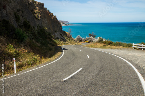 Foto Murales Road leading to a bay. Crystal clear water, amazing landscape. Windy road. Travel, adventure, discover, explore, drive, hike. Sea, ocean, environment, sky.