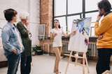 Full length portrait of pretty young woman presenting modern watercolor painting to audience standing in art-studio or gallery - 213675949