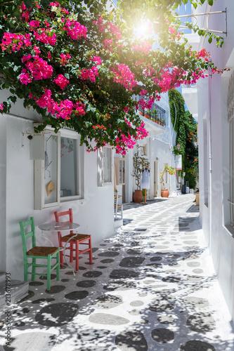 Gasse mit bunten Bougainvillea Blumen, weißen Häusern und farbigen Stühlen in Parikia, Paros, Kykladen, Griechenland