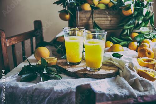 POMARAŃCZOWY. Koncepcja Haervest. Sok pomarańczowy, pełne pudełko pomarańczowe owoce i gałęzie drzewa pomarańczowego na stole z obrusy