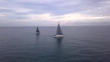 Aerial rotation of two sailboats racing into shore - 213696590