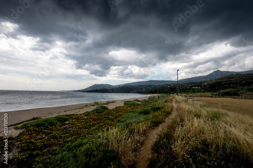 A narrow path on the beach in the dark weather.