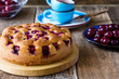 Cherry cake and fresh summer berries on rustic table