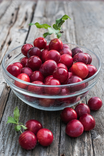 Foto Murales Red greengage in a glass bowl