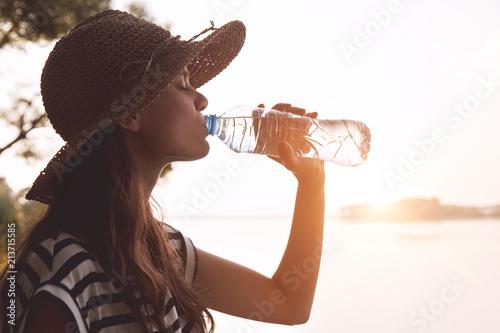 Foto Murales Woman drinking water in summer morning sun