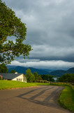 Idyllic rural landscape with cottage house,tree and driveway at sunset with distant mountains and lake.Cloudy skies and soft light complete this relaxed countryside scenery. - 213717584