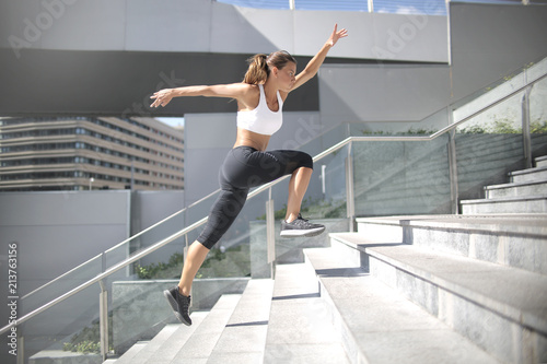 Sportive woman running up on stairs - 213763156