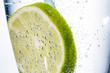 Scheibe einer Limone mit Mineralwasser in Glas - 213765114