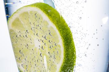 Scheibe einer Limone mit Mineralwasser in Glas