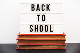 Back to school written in a light box on top of a pile of old  books - 213766941