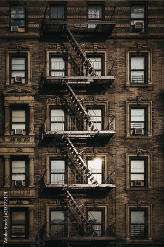 Foto Murales Facade of a typical New York block of flats with fire escape at the front, sun reflects in the windows.