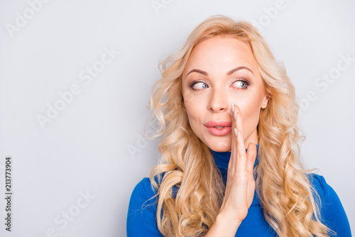 Leinwandbild Motiv Portrait of pretty, trendy, charming, lovely, nice, sexy, cute, blonde woman in blue turtleneck isolated on grey background cover mouth with palm looking to the side whispering gossips