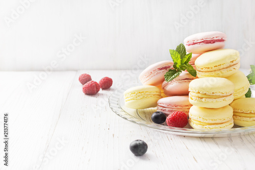 Foto Spatwand Macarons Different types of macarons on white wooden table. Copyspace.