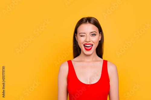 Leinwandbild Motiv Portrait of foxy lovely and funny girl winking with one eye and having beaming smile red pomade lipstick isolated on vivid yellow background