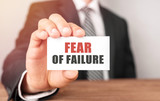 Businessman holding a card with text Fear of Failure - 213791338