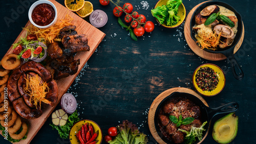 Food on a wooden table. Baked sausages, ribs and meatballs. Top view. Free space for your text.