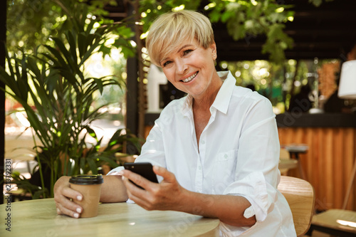 Happy mature woman holding mobile phone