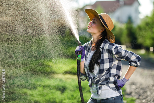 Foto Murales Young woman having fun while watering plants in garden center