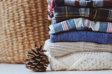 fall casual woman fashion clothes set. Stack of plaid shirts and knitted sweaters with pine cone and basket on background. Cozy stylish womanswear. - 213793799