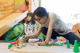 Cute girl with a serious facial expression playing with a wooden train circuit on the floor, during free playtime in the classroom of a modern kindergarten - 213800549