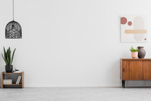 """Постер, картина, фотообои """"Retro, wooden cabinet and a painting in an empty living room interior with white walls and copy space place for a sofa. Real photo."""""""
