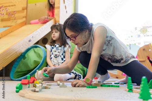 Cute girl with a serious facial expression playing with a wooden train circuit on the floor, during free playtime in the classroom of a modern kindergarten