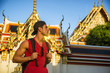 Young handsome man holding backpack standing in Grand Palace. In Bangkok, Thailand. Vertical outdoors shot at dusk - 213802798