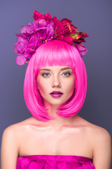 close-up portrait of beautiful young woman with pink bob cut and flowers in hair looking at camera isolated on violet