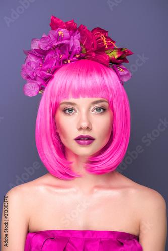 Close-up portret pięknej młodej kobiety z różowym cięciem bob i kwiaty we włosach patrząc na kamery odizolowane na fioletowo