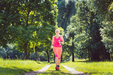 Woman running down a path on grass meadow with weight dumbbells - 213803399