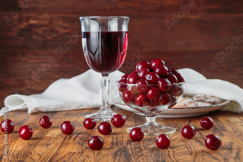 Foto Murales cherry juice in a glass on a high leg against the background of ripe cherries