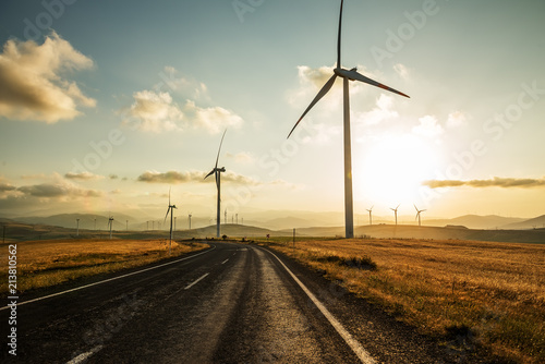 The road runs away from the hills and wind generators.