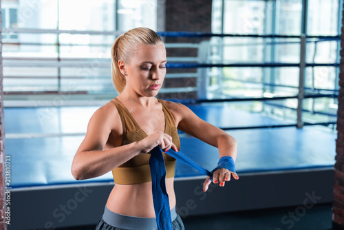 Sport bra. Blonde-haired professional strong female athlete wearing sport bra working out in modern light gym - 213810713
