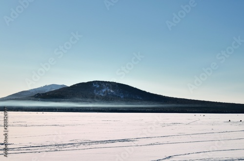 Mountain and forest on background of blue sky and snow. Winter landscape - 213826997