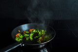 Fry the broccoli and carrots. Vegetarian dish. Process of cooking. - 213831920